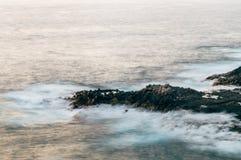 Δύσκολη ακτή και υπερφυσικά ομαλά κύματα από το ηλιοβασίλεμα Στοκ φωτογραφία με δικαίωμα ελεύθερης χρήσης