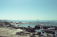 Δύσκολη ακτή της Μεσογείου με ένα σκάφος στον ορίζοντα Στοκ Φωτογραφίες