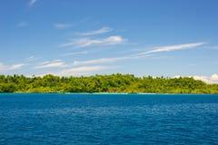Δύσκολη ακτή του νησιού που επισημαίνεται από τα νησάκια και που καλύπτεται από την πυκνή πολύβλαστη πράσινη ζούγκλα στη ζωηρόχρω Στοκ Εικόνα
