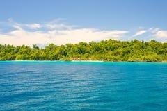 Δύσκολη ακτή του νησιού που επισημαίνεται από τα νησάκια και που καλύπτεται από την πυκνή πολύβλαστη πράσινη ζούγκλα στη ζωηρόχρω Στοκ φωτογραφίες με δικαίωμα ελεύθερης χρήσης
