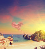 Δύσκολη παραλία στο ηλιοβασίλεμα με το σύννεφο με μορφή καρδιάς Στοκ εικόνες με δικαίωμα ελεύθερης χρήσης
