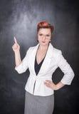 Δύσπιστος δάσκαλος στα γυαλιά που παρουσιάζουν σε κάτι από το δάχτυλο Στοκ Εικόνες