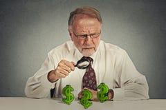 Δύσπιστο επιχειρησιακό άτομο που εξετάζει μέσω της ενίσχυσης - γυαλί το σύμβολο σημαδιών δολαρίων Στοκ εικόνα με δικαίωμα ελεύθερης χρήσης
