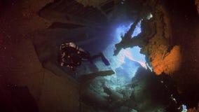 Δύτης καμεραμάν που κολυμπά στα συντρίμμια σκαφών υποβρύχια της Ερυθράς Θάλασσας απόθεμα βίντεο