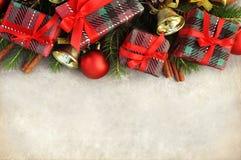 Δώρα και κόκκινα παρόντα κιβώτια στο υπόβαθρο κλάδων έλατου στοκ εικόνες