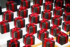 Δώρα στα μαύρα κουτιά με τις κόκκινες κορδέλλες Στοκ Εικόνες