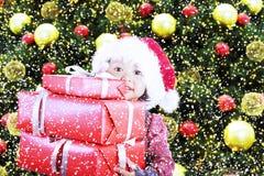 Δώρα Χριστουγέννων από το κορίτσι κάτω από το δέντρο πεύκων Στοκ εικόνα με δικαίωμα ελεύθερης χρήσης
