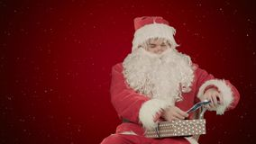Δώρα Χριστουγέννων εκμετάλλευσης Άγιου Βασίλη στο κόκκινο υπόβαθρο με το χιόνι Στοκ εικόνες με δικαίωμα ελεύθερης χρήσης
