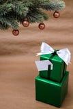 Δώρα Χριστουγέννων κάτω από το διακοσμημένο κλάδο έλατου Στοκ Εικόνες