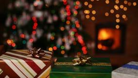 Δώρα Χριστουγέννων μπροστά από την εστία και μουτζουρωμένα φω'τα στο χριστουγεννιάτικο δέντρο απόθεμα βίντεο