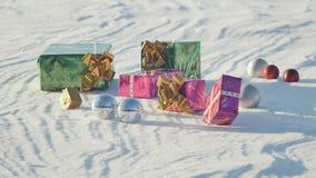 Δώρα Χριστουγέννων σε έναν τομέα στο χιόνι σε έναν ηλιόλουστο, παγωμένο και σαφή καιρό υπαίθρια Ζωτικότητα των δώρων ανάδυσης car φιλμ μικρού μήκους