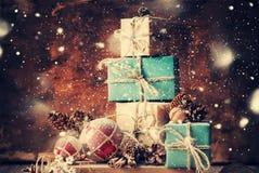 Δώρα Χριστουγέννων στο ξύλινο υπόβαθρο Συρμένο χιόνι Στοκ Φωτογραφία