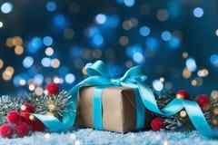 Δώρο ή παρόν κιβώτιο, χιονώδεις δέντρο έλατου και διακόσμηση Χριστουγέννων στο μαγικό μπλε υπόβαθρο Νέα ευχετήρια κάρτα έτους με  Στοκ εικόνες με δικαίωμα ελεύθερης χρήσης