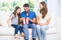 Δώρο ανοίγματος ατόμων καθμένος στον καναπέ με την οικογένεια στοκ εικόνες με δικαίωμα ελεύθερης χρήσης