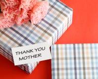 Δώρο και ρόδινο λουλούδι γαρίφαλων στο ρόδινο υπόβαθρο Στοκ Εικόνες