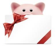 Δώρο καρτών με τη piggy τράπεζα, κόκκινο τόξο κορδελλών, που απομονώνεται στο λευκό Στοκ εικόνα με δικαίωμα ελεύθερης χρήσης