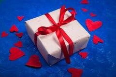 Δώρο με το κώλυμα και πολλές κόκκινες καρδιές εγγράφου στο μπλε backg Στοκ φωτογραφία με δικαίωμα ελεύθερης χρήσης