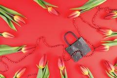 Δώρο, πώληση, έννοια αγορών Σύνθεση τουλιπών με την τσάντα αγορών εγγράφου στο κόκκινο υπόβαθρο Επίπεδος βάλτε, τοπ άποψη στοκ φωτογραφία