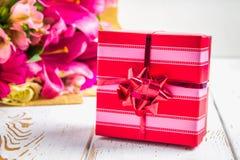 Δώρο σε ένα κιβώτιο και μια ανθοδέσμη των λουλουδιών σε έναν άσπρο ξύλινο πίνακα το όμορφο κέικ γενεθλίων μπαλονιών αφροαμερικάνω Στοκ Φωτογραφίες