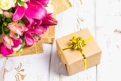 Δώρο σε ένα κιβώτιο και μια ανθοδέσμη των λουλουδιών σε έναν άσπρο ξύλινο πίνακα το όμορφο κέικ γενεθλίων μπαλονιών αφροαμερικάνω Στοκ φωτογραφίες με δικαίωμα ελεύθερης χρήσης