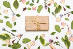 Δώρο στο πλαίσιο από τα λουλούδια και τα φύλλα στοκ εικόνες