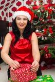 Δώρο Χριστουγέννων ανοίγματος γυναικών Στοκ Εικόνες