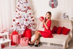 Δώρο Χριστουγέννων Ευτυχής έκπληκτη όμορφη ξανθή γυναίκα που ανοίγει το γ Στοκ Φωτογραφίες