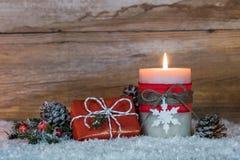 Δώρο Χριστουγέννων και καίγοντας κερί στο χιόνι Στοκ Φωτογραφία