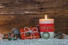 Δώρο Χριστουγέννων και καίγοντας κερί στο χιόνι Στοκ εικόνα με δικαίωμα ελεύθερης χρήσης