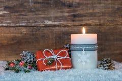 Δώρο Χριστουγέννων και καίγοντας κερί στο χιόνι Στοκ φωτογραφία με δικαίωμα ελεύθερης χρήσης