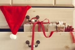 Δώρο Χριστουγέννων και καπέλο Άγιου Βασίλη στο συρτάρι κομμών Στοκ εικόνα με δικαίωμα ελεύθερης χρήσης
