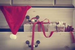 Δώρο Χριστουγέννων και καπέλο Άγιου Βασίλη στο συρτάρι κομμών Στοκ Εικόνες