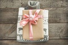 Δώρο Χριστουγέννων με τη ρόδινη κορδέλλα και γκρίζο πουλόβερ στην ξύλινη επιφάνεια Έννοια Χριστουγέννων Στοκ φωτογραφίες με δικαίωμα ελεύθερης χρήσης