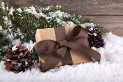 Δώρο Χριστουγέννων με τους κώνους Pne και κλάδος δέντρων στη χιονώδη επιφάνεια στοκ εικόνες