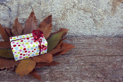 Δώρο Χριστουγέννων με το κόκκινο τόξο στον ξύλινο πίνακα ζωηρόχρωμος ξηρός ανασκόπησης φθινοπώρου βγάζει φύλλα τα φύλλα στοκ εικόνα
