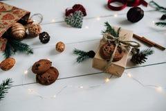Δώρο Χριστουγέννων που διακοσμείται: κλαδάκια έλατου, μπισκότα, κώνος πεύκων και φω'τα Χριστουγέννων Στοκ Φωτογραφία
