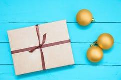 Δώρο Χριστουγέννων σε ένα κιβώτιο και τρία χρυσά στοκ φωτογραφία