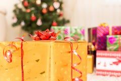 Δώρο Χριστουγέννων στο χρυσό κιβώτιο στο υπόβαθρο του δέντρου Στοκ Φωτογραφία