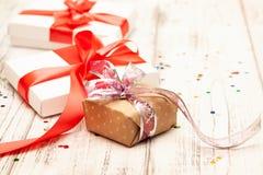 Δώρο boxex με τη λεπτά κόκκινα κορδέλλα και το κομφετί στο παλαιό άσπρο ξύλινο τ στοκ φωτογραφίες με δικαίωμα ελεύθερης χρήσης