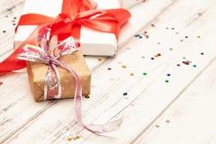 Δώρο boxex με τη λεπτά κόκκινα κορδέλλα και το κομφετί στο παλαιό άσπρο ξύλινο τ στοκ εικόνα