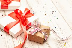 Δώρο boxex με τη λεπτά κόκκινα κορδέλλα και το κομφετί στο παλαιό άσπρο ξύλινο τ στοκ φωτογραφία