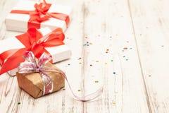 Δώρο boxex με τη λεπτά κόκκινα κορδέλλα και το κομφετί στο παλαιό άσπρο ξύλινο τ στοκ φωτογραφία με δικαίωμα ελεύθερης χρήσης