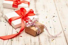 Δώρο boxex με τη λεπτά κόκκινα κορδέλλα και το κομφετί στο παλαιό άσπρο ξύλινο τ στοκ εικόνες