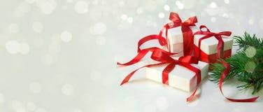 Δώρο ` s Χριστουγέννων στο άσπρο κιβώτιο με την κόκκινη κορδέλλα στο ελαφρύ υπόβαθρο Νέο έμβλημα σύνθεσης διακοπών έτους διάστημα Στοκ εικόνες με δικαίωμα ελεύθερης χρήσης