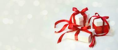 Δώρο ` s Χριστουγέννων στο άσπρο κιβώτιο με την κόκκινη κορδέλλα στο ελαφρύ υπόβαθρο Νέο έμβλημα σύνθεσης διακοπών έτους διάστημα στοκ εικόνες