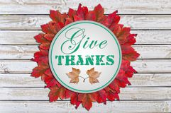 Δώστε τις ευχαριστίες που γράφονται στον κύκλο μέσα στο κόκκινο άσπρο ξύλο φύλλων Στοκ Εικόνες