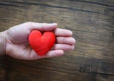 Δώστε το άτομο αγάπης που κρατά ότι η κόκκινη καρδιά στα χέρια για την ημέρα βαλεντίνων αγάπης δίνει τη βοήθεια δίνει τη ζεστασιά στοκ φωτογραφία