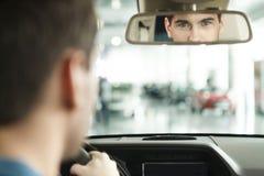 Είμαι βέβαιος με το αυτοκίνητό μου. Νεαροί άνδρες Hansome που κάθονται στο μέτωπο Στοκ Εικόνα
