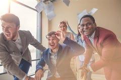 Είμαστε οι νικητές επιχειρηματίες που έχουν τη διασκέδαση συναγωνιμένος στις καρέκλες γραφείων Στοκ Φωτογραφίες