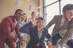 Είμαστε οι νικητές επιχειρηματίες που έχουν τη διασκέδαση συναγωνιμένος στις καρέκλες γραφείων Στοκ Εικόνα